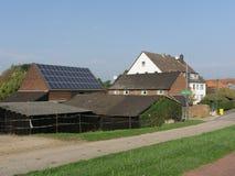 Κεραμωμένες στέγες των αγροτικών σπιτιών πετρών με μια ηλιακή μπαταρία στα ευρωπαϊκά προάστια στοκ εικόνα