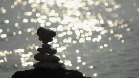 Κεραμωμένη σκιαγραφία βράχων με τα σπινθηρίσματα ήλιων στο νερό πίσω φιλμ μικρού μήκους