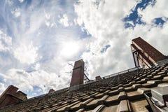 Κεραμωμένη στέγη με τα σκούρο παρτοκαλί τούβλα και τις κίτρινες καπνοδόχους ενάντια στο δ Στοκ Εικόνες