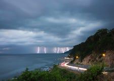 Κεραυνός αστραπής στη θάλασσα στο λυκόφως με το φωτισμό από τα αυτοκίνητα Στοκ Εικόνες