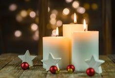Κεριά εμφάνισης με τη διακόσμηση Χριστουγέννων και το λαμπιρίζοντας υπόβαθρο φω'των στοκ φωτογραφίες