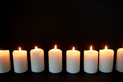 Κεριά που καίνε στο σκοτάδι πέρα από το μαύρο υπόβαθρο Στοκ Εικόνες