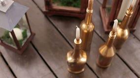 Κεριά στα χρυσά μπουκάλια στο γαμήλιο ντεκόρ φιλμ μικρού μήκους
