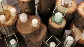Κεριά στη διακοσμημένη στάση βάζων στα κούτσουρα στο γάμο φιλμ μικρού μήκους