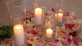 Κεριά στις φιάλες γυαλιού μεταξύ των ροδαλών πετάλων γάμος απόθεμα βίντεο