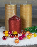 Κεριά Χριστουγέννων στο χιόνι με τις ζωηρόχρωμες σφαίρες Στοκ εικόνες με δικαίωμα ελεύθερης χρήσης