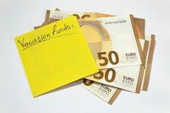Κεφάλαια διακοπών κατοχή των χρημάτων σωρός της κίτρινης κολλώδους σημείωσης 50 ευρώ στοκ φωτογραφία με δικαίωμα ελεύθερης χρήσης