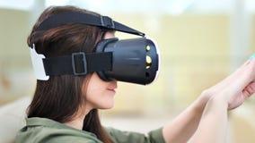 Κεφάλι κινηματογραφήσεων σε πρώτο πλάνο της έκπληκτης νέας γυναίκας που φορά τα γυαλιά εικονικής πραγματικότητας που παίζουν στο  απόθεμα βίντεο