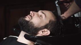 Κεφάλι ατόμων πλύσης κουρέων στο barbershop απόθεμα βίντεο
