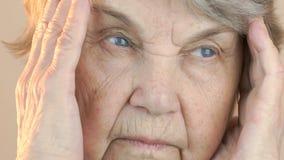 Κεφάλι εκμετάλλευσης ηλικιωμένων γυναικών με τα χέρια λόγω του πονοκέφαλου απόθεμα βίντεο