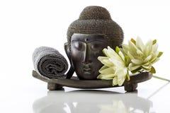 Κεφάλι του Βούδα σε ένα άσπρους υπόβαθρο, μια πετσέτα και έναν λωτό Στοκ Φωτογραφίες
