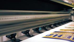 Κεφαλή εκτύπωσης του βιομηχανικού εκτυπωτή που κάνει το ζωηρόχρωμο έμβλημα με τις επιγραφές απόθεμα βίντεο