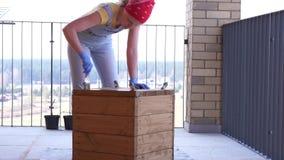 Κηπουρική και δενδροκηποκομία - η γυναίκα στο πεζούλι χρωματίζει το ξύλινο κιβώτιο για τη φύτευση απόθεμα βίντεο