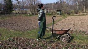 Κηπουρός γυναικών με τον πόνο στην πλάτη στον τομέα απόθεμα βίντεο