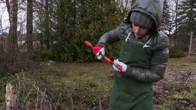 Κηπουρός γυναικών με το ψαλίδι κοντά στο σωρό κλάδων φιλμ μικρού μήκους