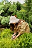 Κηπουρός κοριτσιών στα λειτουργώντας ενδύματα και το καπέλο αχύρου Στοκ Εικόνες