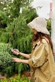 Κηπουρός κοριτσιών στα scissoors κήπων περικοπών λειτουργώντας ενδυμάτων και καπέλων αχύρου αειθαλή Στοκ εικόνα με δικαίωμα ελεύθερης χρήσης