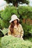 Κηπουρός κοριτσιών στα scissoors κήπων περικοπών λειτουργώντας ενδυμάτων και καπέλων αχύρου αειθαλή Στοκ φωτογραφία με δικαίωμα ελεύθερης χρήσης