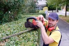 Κηπουρός που χρησιμοποιεί έναν κουρευτή ζώων φρακτών στον κήπο Στοκ Εικόνα