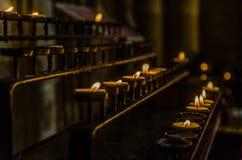Κηροπήγια με τα κεριά αναμμένα και μισό-που εξαφανίζονται που είναι προσφορές που αφήνονται από θρησκευτικό τον πιστό στοκ φωτογραφίες