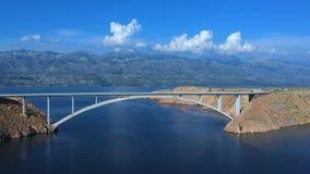 Κηφήνας που ανυψώνει κοντά στη γέφυρα πέρα από την μπλε θάλασσα με το μπλε ουρανό και τα άσπρα σύννεφα απόθεμα βίντεο