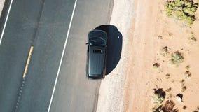 Κηφήνας που αυξάνεται γρήγορα επάνω από το αυτοκίνητο με το sunroof ανοικτό, στεμένος στο δρόμο ασφάλτου στη μέση της ξηράς δύσκο απόθεμα βίντεο
