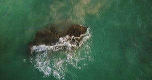 Κηφήνας που κινείται αργά πέρα από το διαφανές κύμα πράσινης θάλασσας που συντρίβει πέρα από μια μεγάλη πέτρα σκοπέλων κοραλλιογε απόθεμα βίντεο