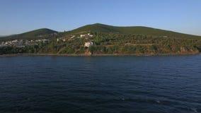 Κηφήνας που πετά από τη θάλασσα στην ακτή με τα σπίτια στην προκυμαία, Ελλάδα απόθεμα βίντεο