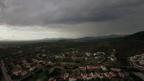 Κηφήνας που πετά και που κατεβαίνει πέρα από την πόλη, άποψη στα εξοχικά σπίτια και τα πράσινα διαστήματα, Ελλάδα απόθεμα βίντεο