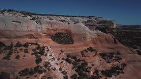 Κηφήνας που πετά μακρυά από το ζεύγος τουριστών που στέκεται στο διάσημο σχηματισμό βράχου αψίδων στο ηλιόλουστο εθνικό πάρκο βου φιλμ μικρού μήκους
