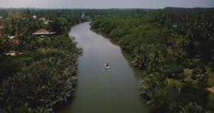 Κηφήνας που πετά προς τα εμπρός πέρα από τη μικρή βάρκα στον όμορφο ευρύ ποταμό που ρέει στην αγριότητα ζουγκλών μεταξύ των τροπι φιλμ μικρού μήκους