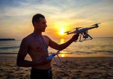 Κηφήνας που πετά στο ηλιοβασίλεμα πέρα από τη θάλασσα Άτομο που προσγε στοκ εικόνες
