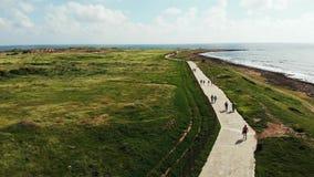 Κηφήνας που πυροβολείται των πεζών που περπατούν και που τρέχουν κατά μήκος της ακτής ακτών Ισχυρά κύματα που χτυπούν τη δύσκολη  απόθεμα βίντεο