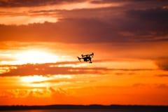 Κηφήνας Quadrocopter με τον τηλεχειρισμό Σκοτεινή σκιαγραφία ενάντια στο ηλιοβασίλεμα colorfull στρέψτε μαλακό εικόνα που τονίζετ Στοκ Εικόνες