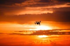 Κηφήνας Quadrocopter με τον τηλεχειρισμό Σκοτεινή σκιαγραφία ενάντια στο ηλιοβασίλεμα colorfull στρέψτε μαλακό εικόνα που τονίζετ στοκ φωτογραφία με δικαίωμα ελεύθερης χρήσης