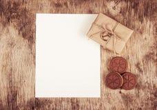 Κιβώτια δώρων και καρδιές μπισκότων σε ένα ξύλινο υπόβαθρο Ένα κενό φύλλο του εγγράφου και ενός δώρου Στοκ φωτογραφίες με δικαίωμα ελεύθερης χρήσης