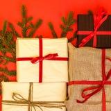 Κιβώτια δώρων κλάδων/κλαδίσκων και Χριστουγέννων του FIR στο κόκκινο υπόβαθρο στοκ φωτογραφία