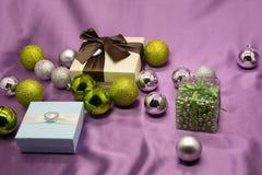 Κιβώτια δώρων με ένα μεγάλο κόκκινο τόξο σε ένα κλίμα bokeh των φω'των κομμάτων αστραπής Νέο δώρο έτους πολυτέλειας Δώρο Χριστουγ Στοκ Φωτογραφίες