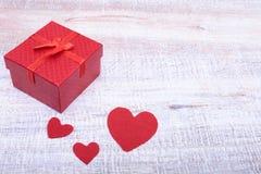 Κιβώτια δώρων με το τόξο και την κόκκινη καρδιά στο ξύλινο υπόβαθρο Στοκ Φωτογραφίες