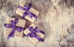Κιβώτια δώρων με το τόξο σατέν στον ξύλινο πίνακα Τύλιγμα δώρων στο eco-ύφος Στοκ Εικόνες