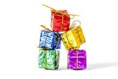 Κιβώτια δώρων σε μια πολύχρωμη συσκευασία που επιδένεται με μια στάση τόξων σε μια κινηματογράφηση σε πρώτο πλάνο στηλών που απομ Στοκ Εικόνες