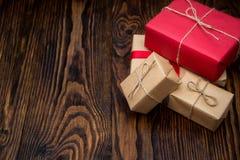 Κιβώτια δώρων στο έγγραφο κοκκίνου και τεχνών για το παλαιό ξύλινο υπόβαθρο Στοκ Εικόνες