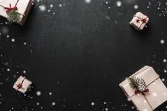 Κιβώτια δώρων στο μαύρο υπόβαθρο Παρουσιάζει στην τέχνη με την κόκκινα κορδέλλα και snowflakes Χριστούγεννα και άλλη έννοια διακο Στοκ φωτογραφία με δικαίωμα ελεύθερης χρήσης