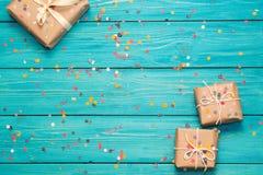 Κιβώτια δώρων στο τυρκουάζ ξύλινο υπόβαθρο με το κομφετί Στοκ Εικόνα