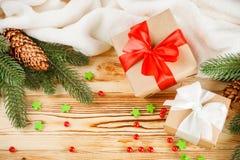 Κιβώτια δώρων τεχνών με την κορδέλλα χρώματος και το τόξο, πράσινο χριστουγεννιάτικο δέντρο, διακοσμήσεις, άσπρο καρό στο ξύλινο  Στοκ Φωτογραφία
