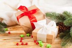 Κιβώτια δώρων τεχνών με την κορδέλλα χρώματος και το τόξο, πράσινο χριστουγεννιάτικο δέντρο, διακοσμήσεις, άσπρο καρό στο ξύλινο  Στοκ Φωτογραφίες