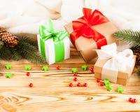 Κιβώτια δώρων τεχνών με την κορδέλλα χρώματος και το τόξο, πράσινο χριστουγεννιάτικο δέντρο, διακοσμήσεις, άσπρο καρό στο ξύλινο  Στοκ εικόνα με δικαίωμα ελεύθερης χρήσης