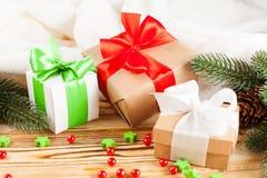 Κιβώτια δώρων τεχνών με την κορδέλλα χρώματος και το τόξο, πράσινο χριστουγεννιάτικο δέντρο, διακοσμήσεις, άσπρο καρό στο ξύλινο  Στοκ εικόνες με δικαίωμα ελεύθερης χρήσης