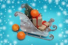 Κιβώτια δώρων Χριστουγέννων εγγράφου τεχνών σε ένα έλκηθρο, τις κλημεντίνες, τους κλάδους έλατου και Snowflakes στοκ εικόνες