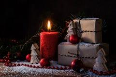 Κιβώτια δώρων Χριστουγέννων και ένα καίγοντας κερί στο χιόνι, που διακοσμείται Στοκ εικόνα με δικαίωμα ελεύθερης χρήσης